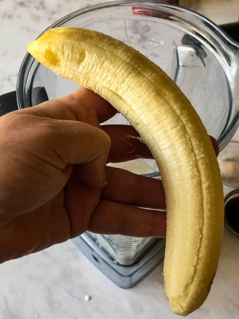 peeled banana in hand showing size and blemish free