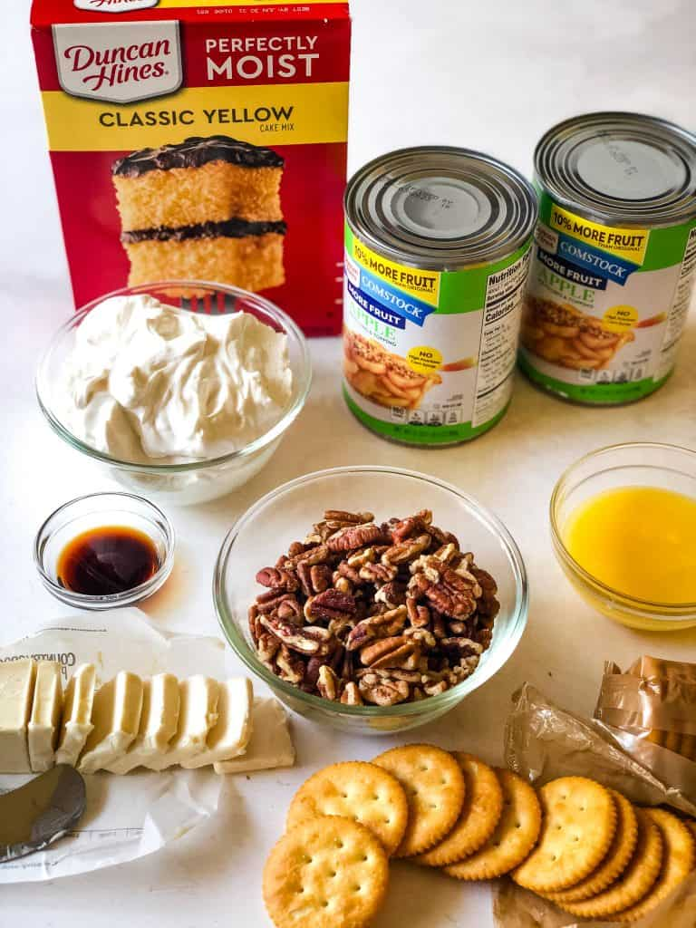 The ingredients for sour cream apple pie dump cake including vegan butter and sour cream, pecans, ritz crackers, apple pie filling , vanilla, and a yellow cake mix