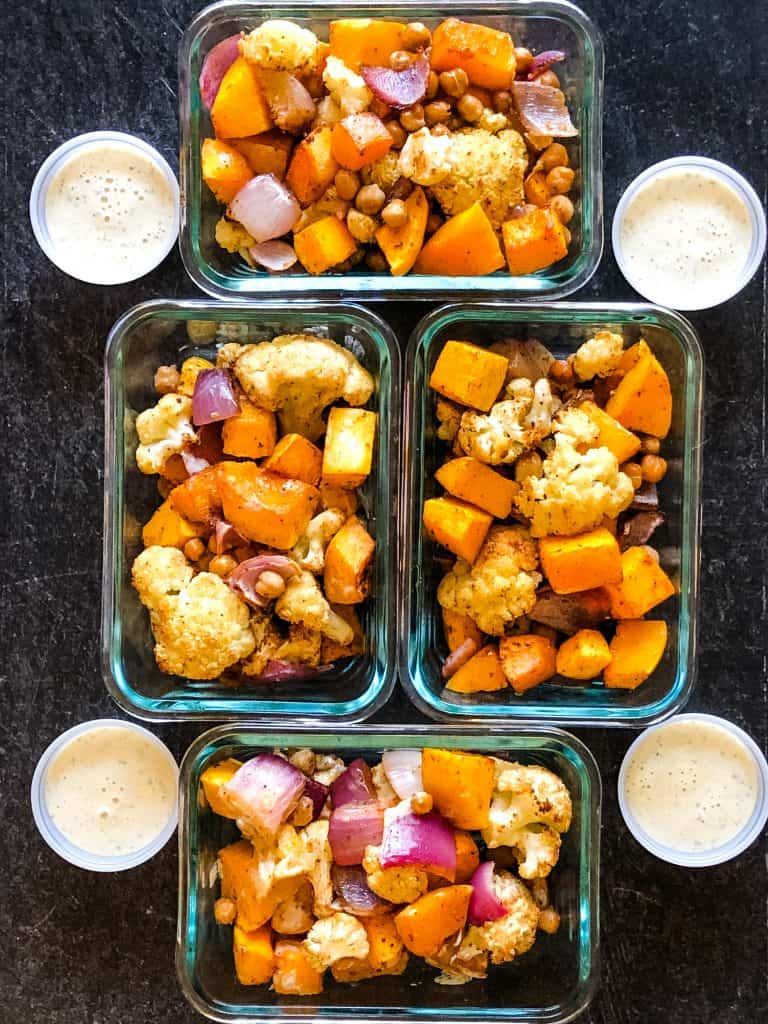 four meal prep containers with roasted butternut squash and cauliflower - four small round containers of jalapeno ranch dressing