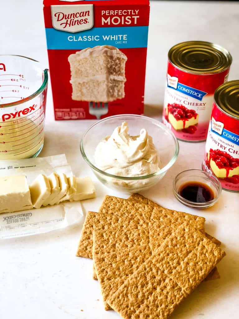 ingredients for cherry cheesecake dump cake including graham crackers, vegan butter, vegan cream cheese, vanilla, cans of cherry pie filling and cake mix