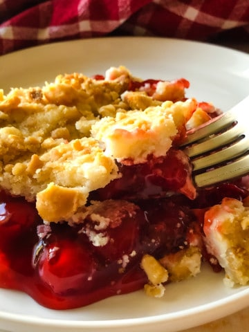 cherry cheesecake dump cake on plate with red checked napkin in background