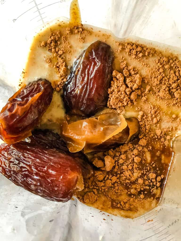 ingredients for chocolate almond ice cream in blender with Medjool dates on top