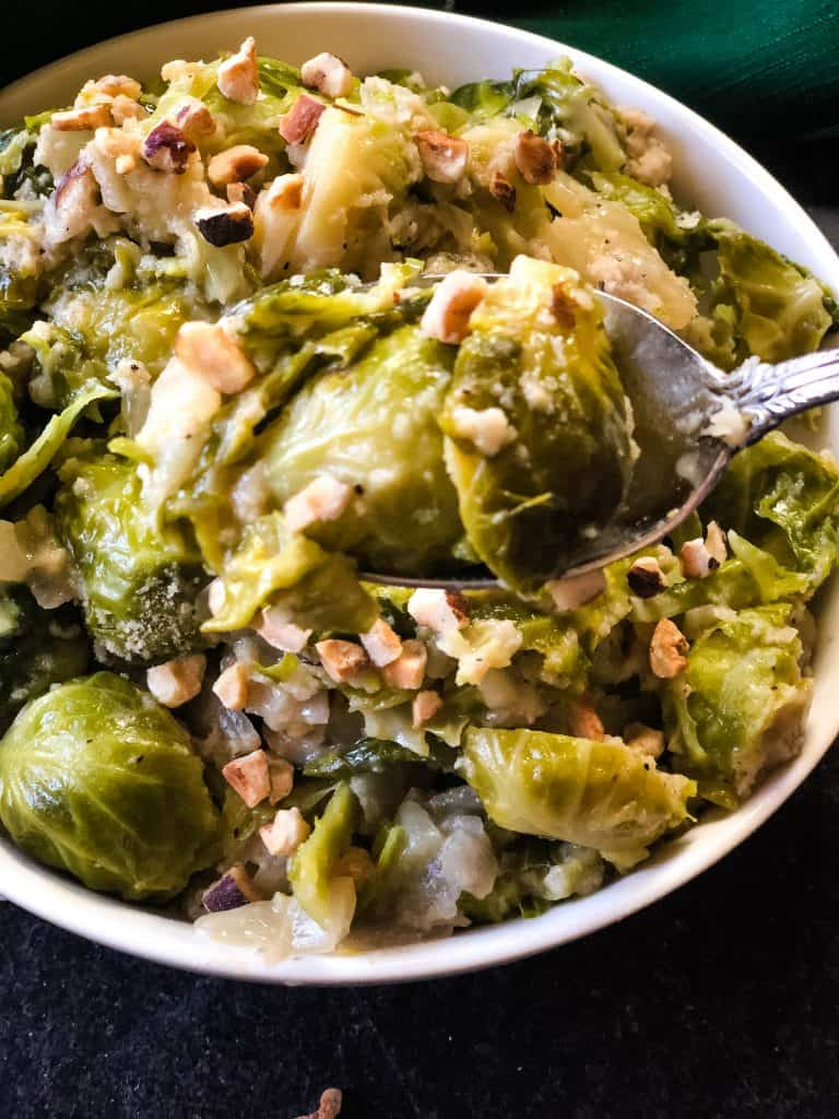 spooning out a portion of brussels sprouts topped with hazelnuts