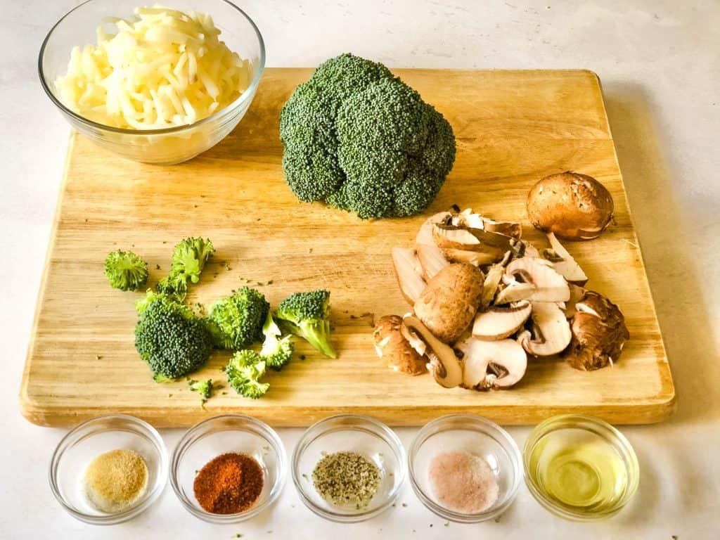 ingredients for roasted vegetables for breakfast bake including hash browns, broccoli, mushrooms, seasonings, and oil