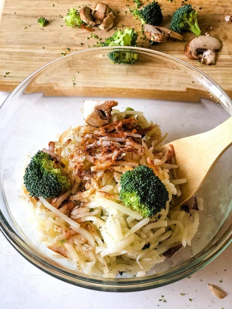veggies in bowl tossed with seasonings for breakfast bake