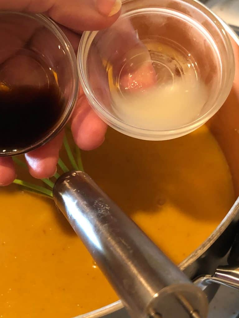 prep cups with vanilla and lemon juice being poured over cooked pumpkin ice cream mixture