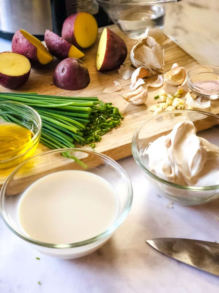 ingredients needed for mashed potatoes including milk, cream cheese, oil, garlic, chives, and red potatoes