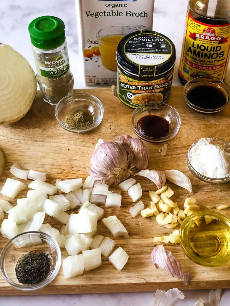 the ingredients for vegan turkey gravy including chopped onions, garlic, oil, cornstarch, liquid aminos, bouillon, poultry seasoning, and dried thyme