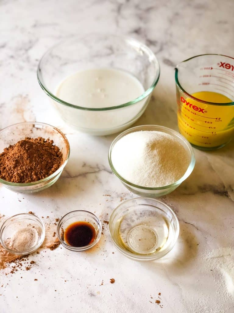 Ingredients needed for vegan chocolate sauce including cocoa, coconut cream, sugar, vegan butter, salt, vanilla, corn syrup