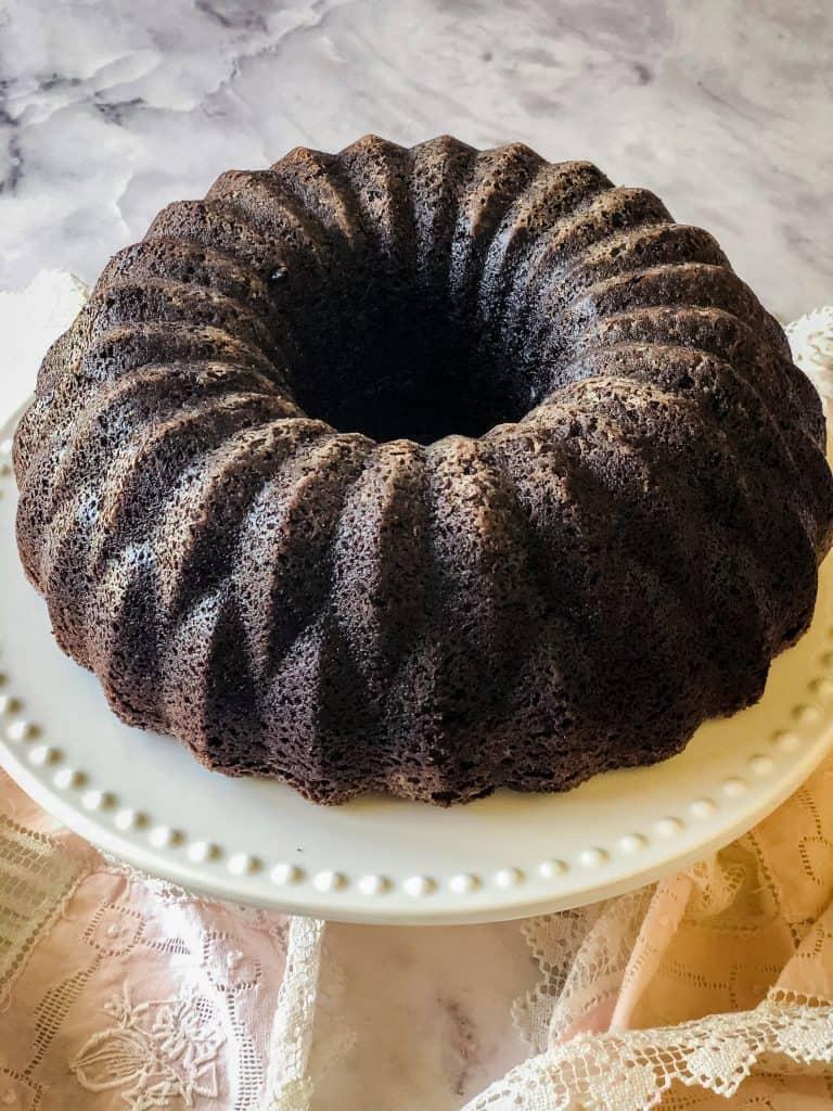 baked and unfrosted bundt cake on white cake dish