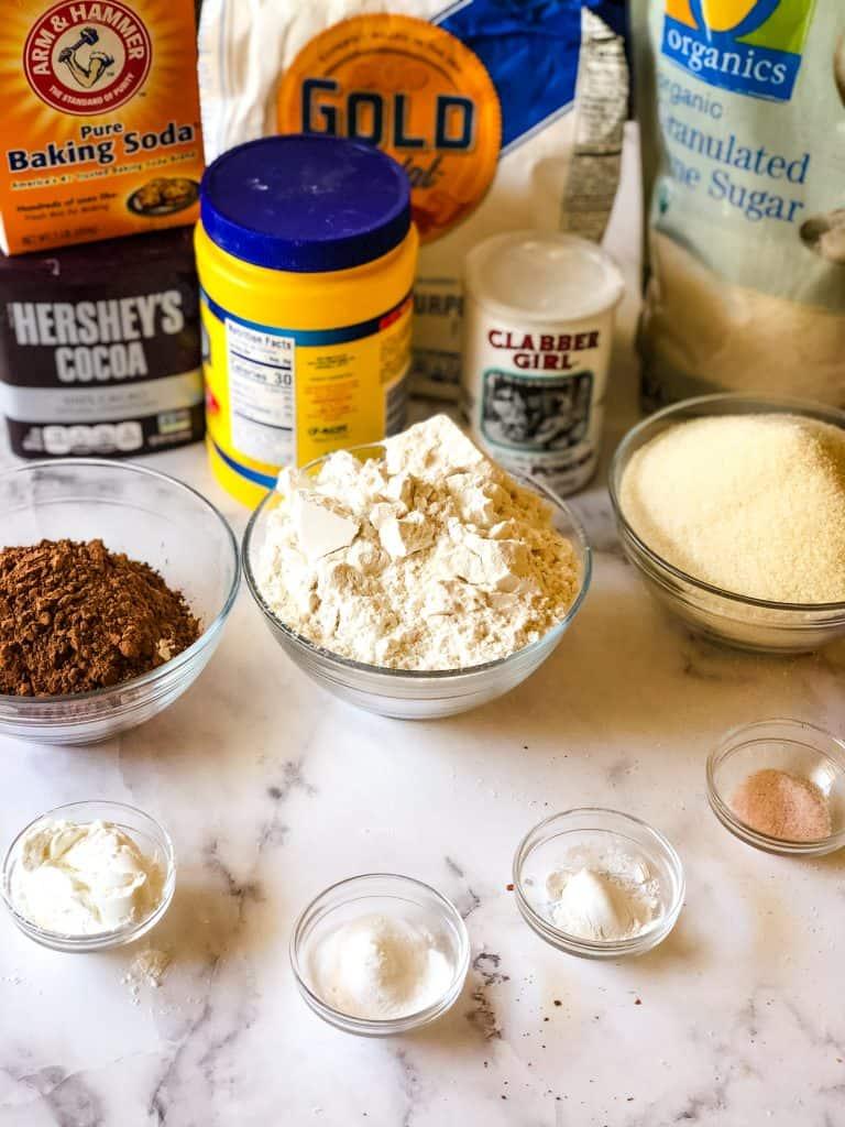 dry ingredients needed to make vegan devil's food including cocoa power, white flour, sugar, cornstarch, baking powder, baking soda, and salt