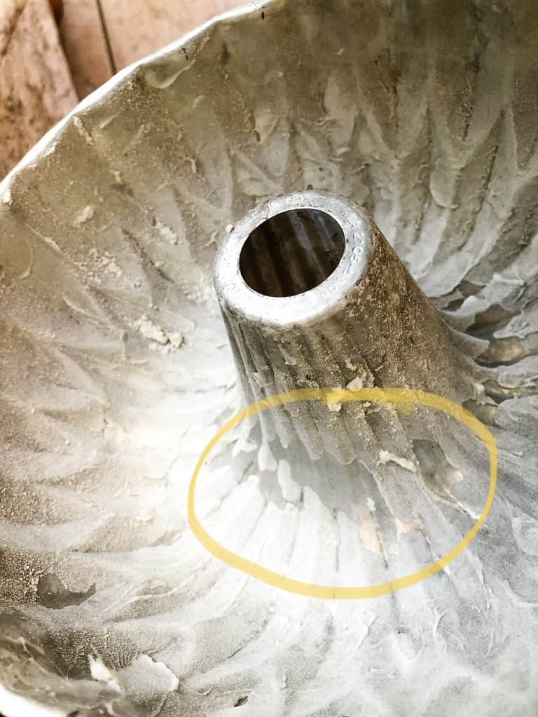 greased and floured bundt pan showing a bare spot that is circled in yellow