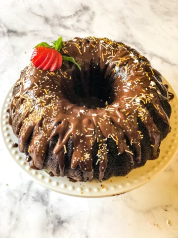 devils food cake frosted with ganache, sprinkles, and a cut strawberry