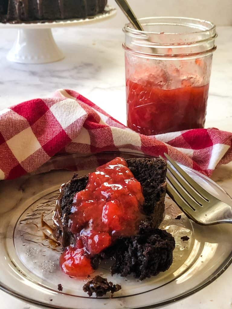 chocolate cake with strawberry toping with jar and cake in background