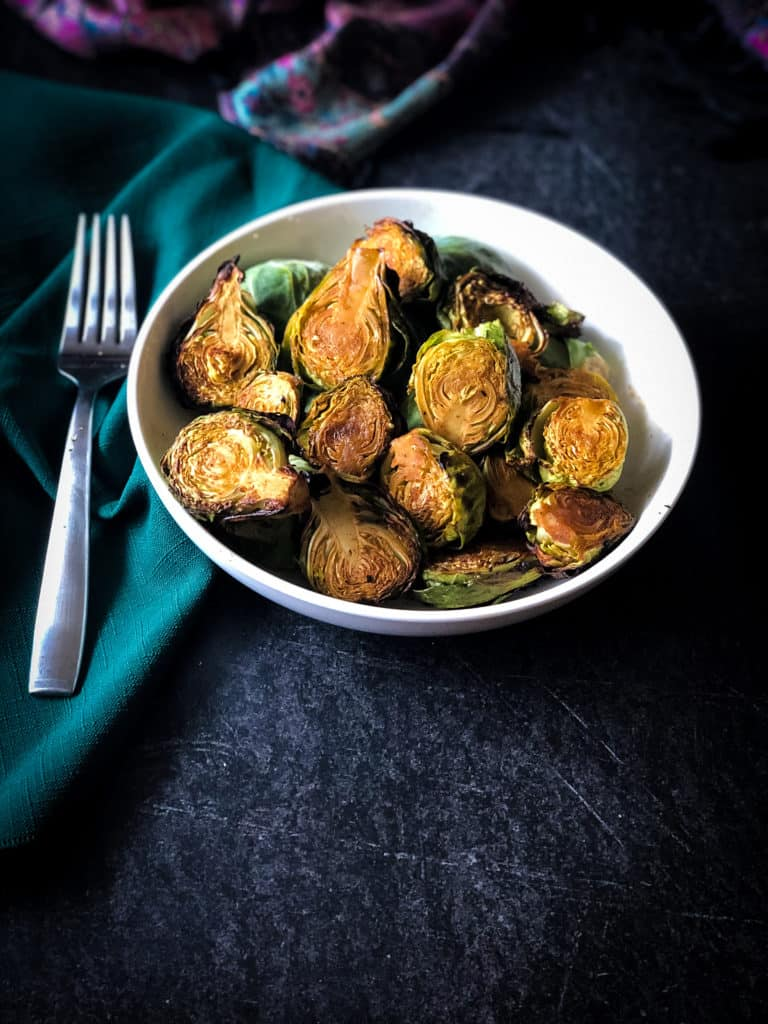 White owl of air-fried Brussels sprouts with fork and green napkin