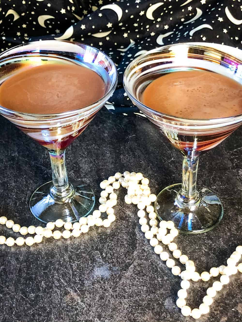 Two elegant martini glasses filled with chocolate martinis made with vegan chocolate liqueur with stars and moon backdrop and white beads in forefront
