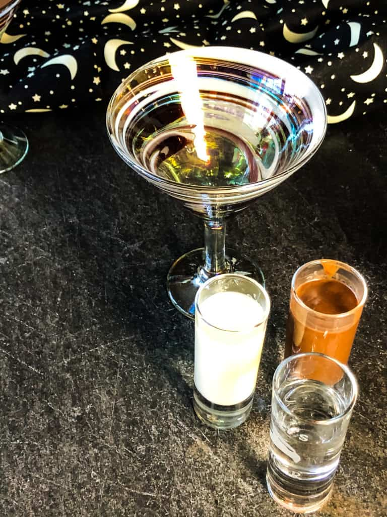 Ingredients needed for chocolate martini including oat milk, vodka, and vegan chocolate liqueur along with martini glass