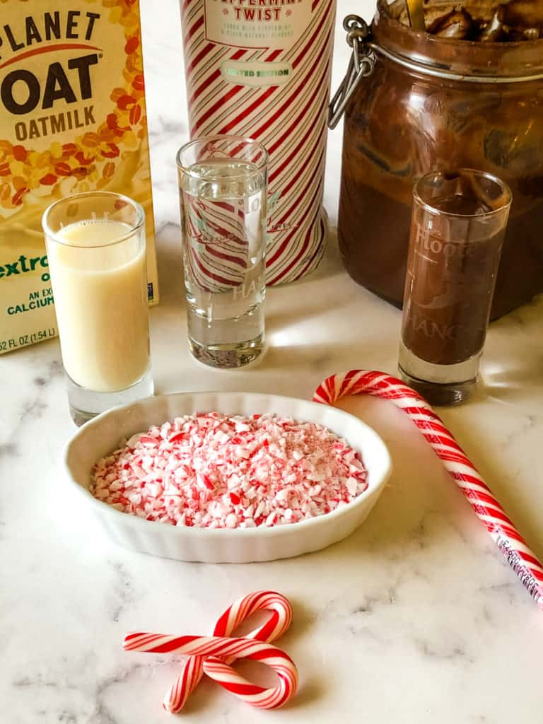 ingredients needed for chocolate peppermint martini including crushed candy canes, oat milk, peppermint vodka, and vegan chocolate liqueur