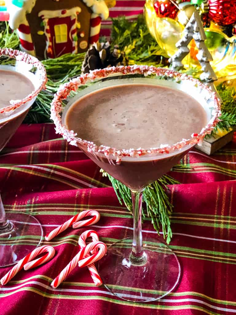 martini glass with chocolate peppermint martini and a candy cane rimmed glass with festive christmas decor in the background