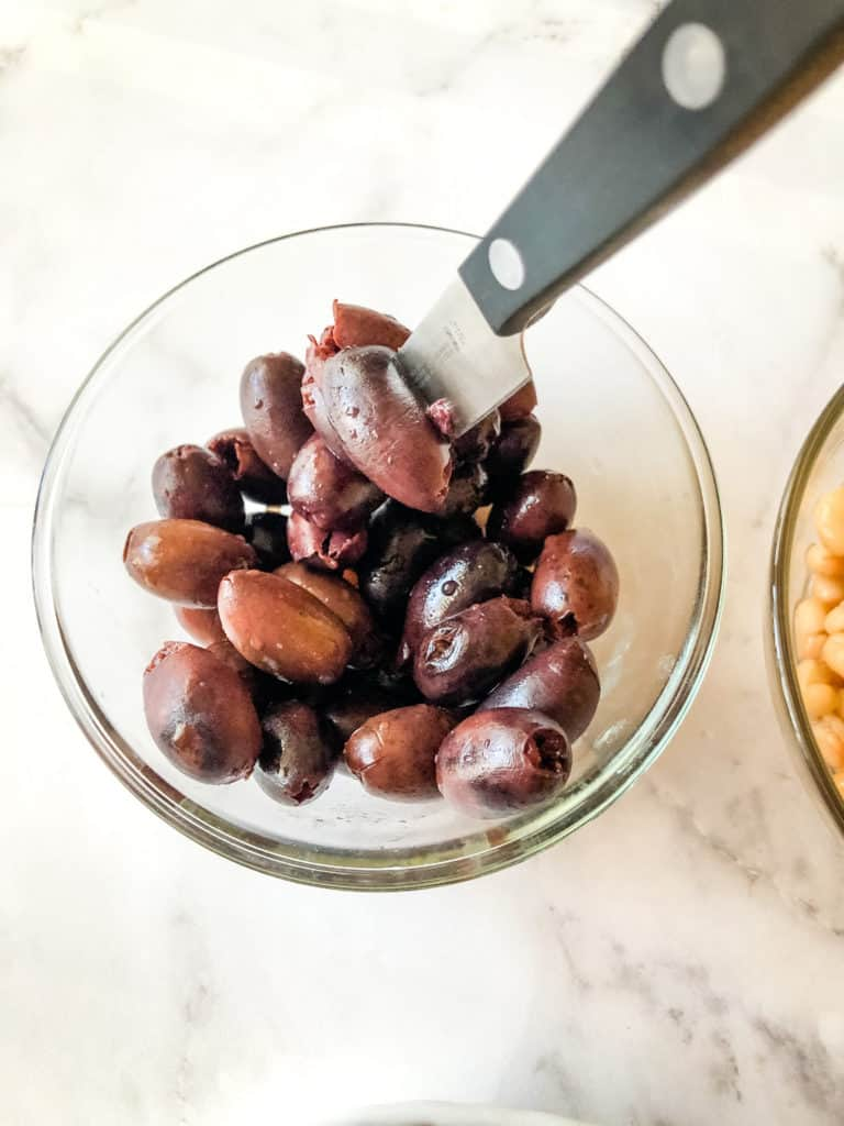 kalamata olives in bowl with knife cutting through the middle
