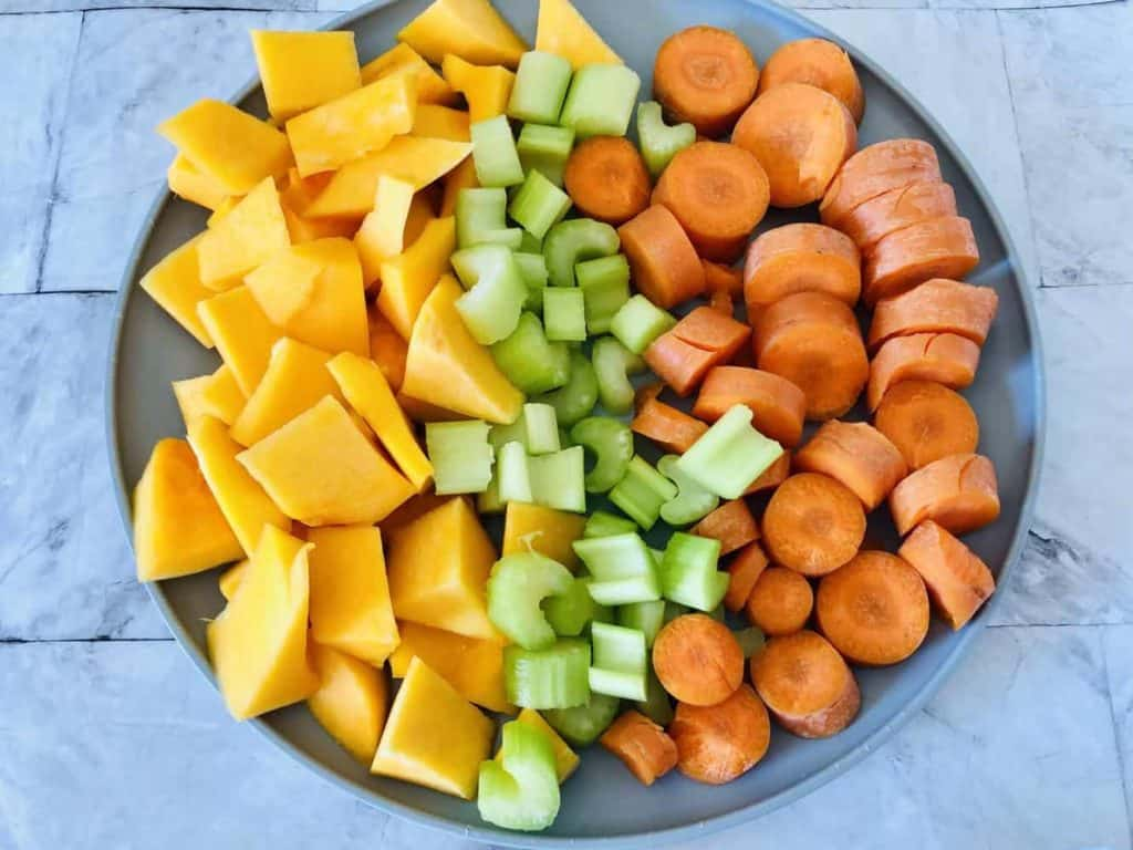 cut butternut squash, celery, and carrots on a plate