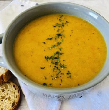 roasted butternut squash soup in bowl with sliced bread on the side