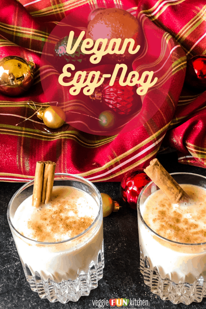 Two glasses of vegan egg-nog with cinnamon sticks against a red plaid background with christmas ornaments. with pinterest text overlay