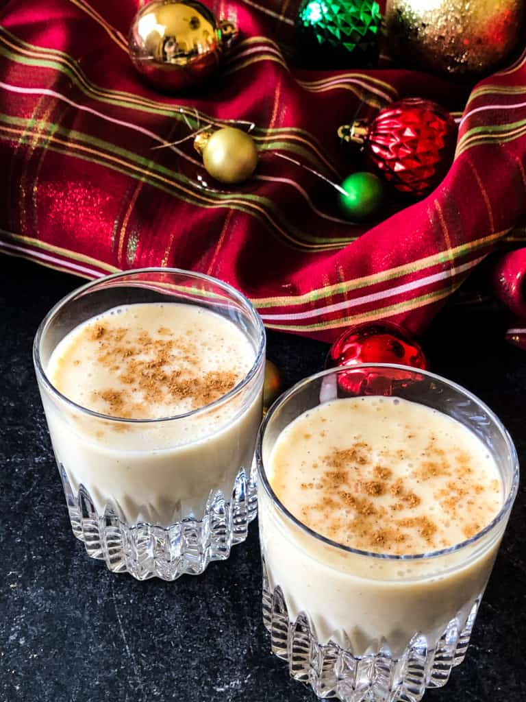 Two glasses of vegan egg-nog against a red plaid background with christmas ornaments.