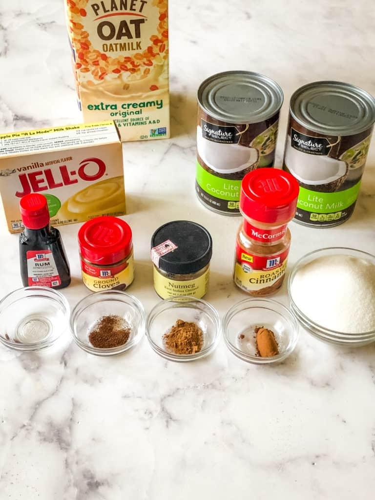 All this ingredients for vegan eggnog including oat milk, vanilla jello, rum flavoring, coconut milk, cloves, nutmeg, cinnamon, and sugar
