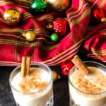 Two glasses of vegan egg-nog with cinnamon sticks against a red plaid background with christmas ornaments.