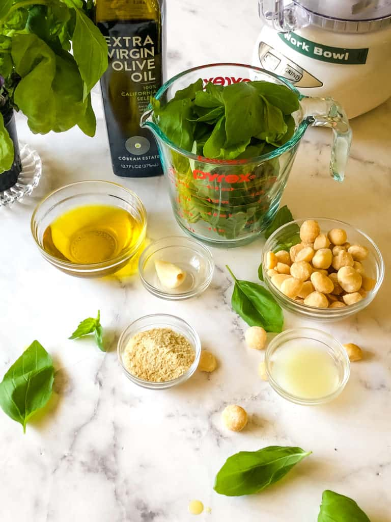 ingredients needed for macadamia nut pesto including olive oil, basil leaves, macadamia nuts, garlic clove, nutritional yeast and lemon juice