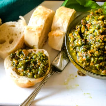 Bowl of pistachio pesto with sliced bread on which to spread this delicious pesto
