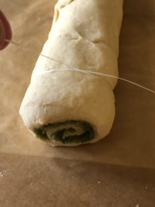 Cutting the pesto rolls with dental floss