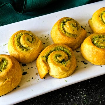 cooked pesto dinner rolls on a white tray