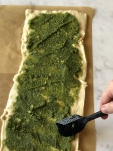 spreading pesto on the rolled out and pinched crescents. Notice that the edge does not have pesto on it.