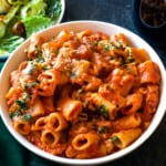 Vegan pasta bake in a dish with salad and bread in the background