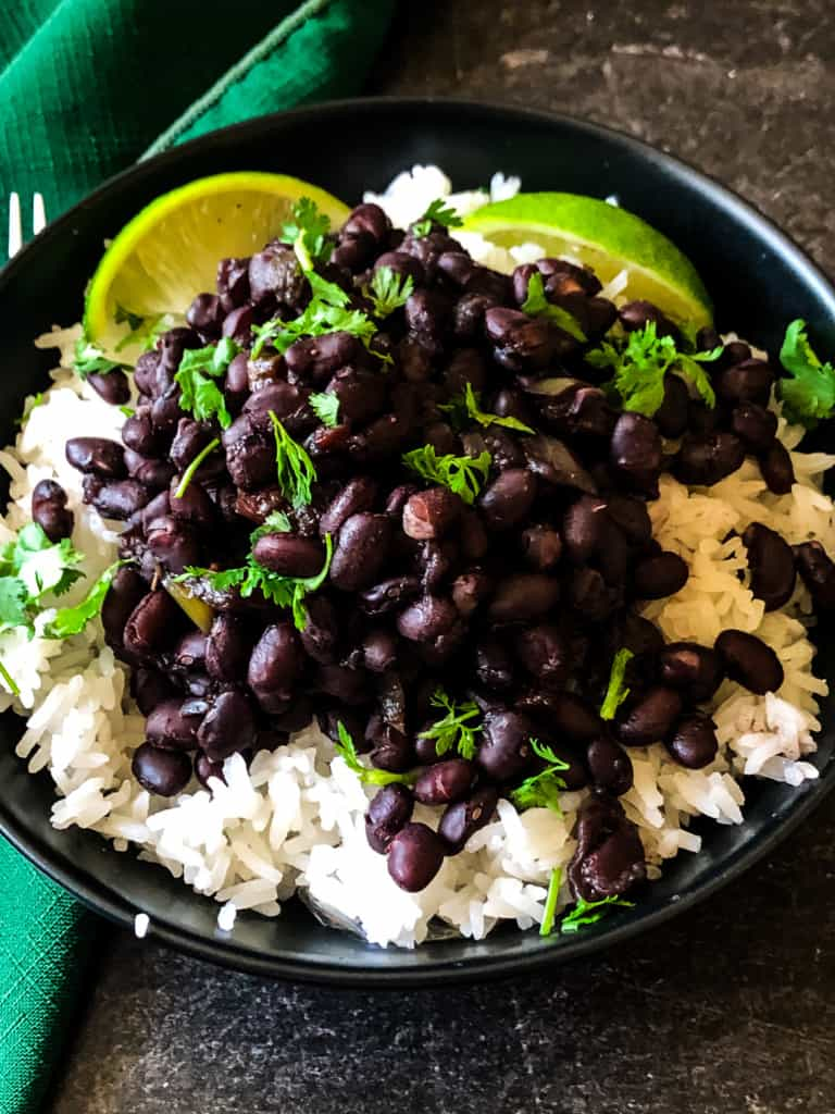 Cuban black beans over rice with limes on the side and cilantro on top