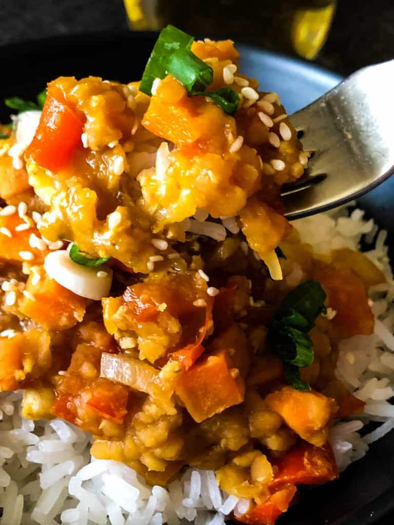 a fork full or cooked red lentils over rice