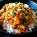 Red lentils on rice in a black bowl