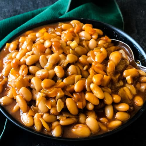 bourbon baked beans in a black bowl