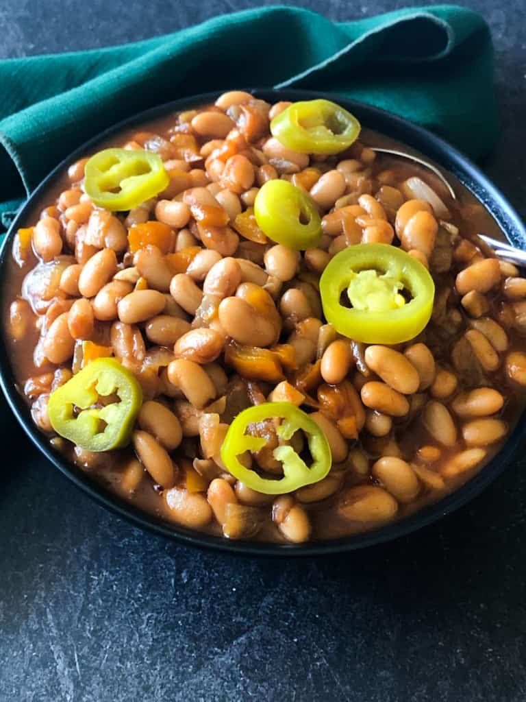 bourbon baked beans in a black bowl topped with pickled jalapenos