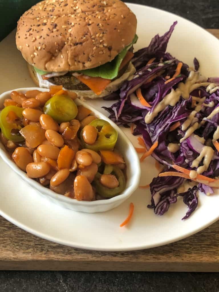 plate with bowl of baked beans, plant burger, and purple slaw