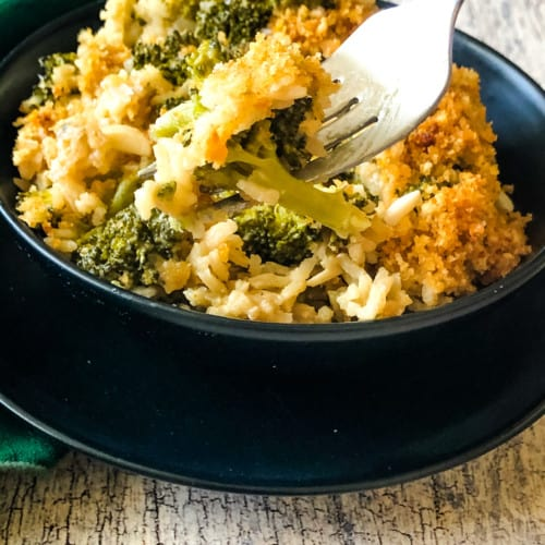 A fork serving up a delicious bite of Broccoli Rice Casserole in black bowl