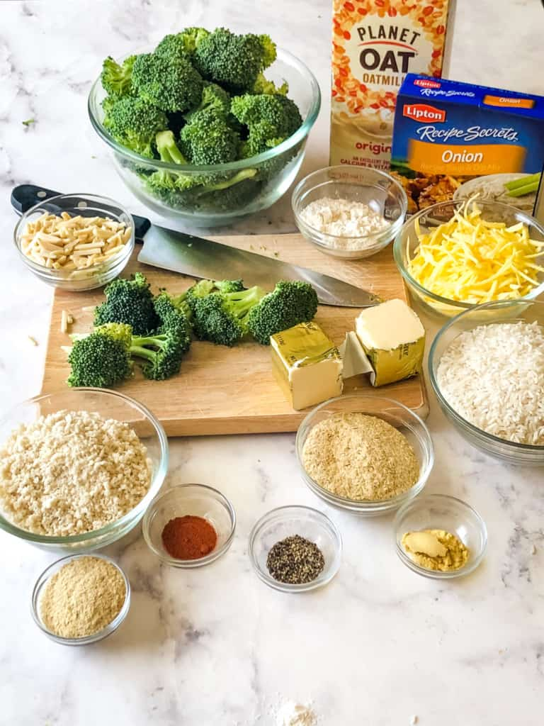 ingredients needed for Broccoli Rice Casserole including cut broccoli, oat milk, Lipton Onion Soup Mix, slivered almonds, vegan butter, vegan shredded cheese, uncooked rice, panko bread crumbs, nutritional yeast, dry mustard, paprika, ground pepper