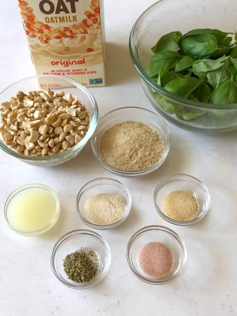 ingredients for creamy basil dressing including raw cashews, oat milk, basil leaves, nutritional yeast, lemon juice, onion and garlic powders, italian seasoning, and salt