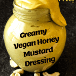 vegan honey mustard dressing in a small jar with an unsightly amount dribbling from the top with raw cashews in the foreground with Pinterest text overlay
