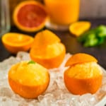 orange sorbet in orange peels in an iced dish with a glass container of orange juice in the background
