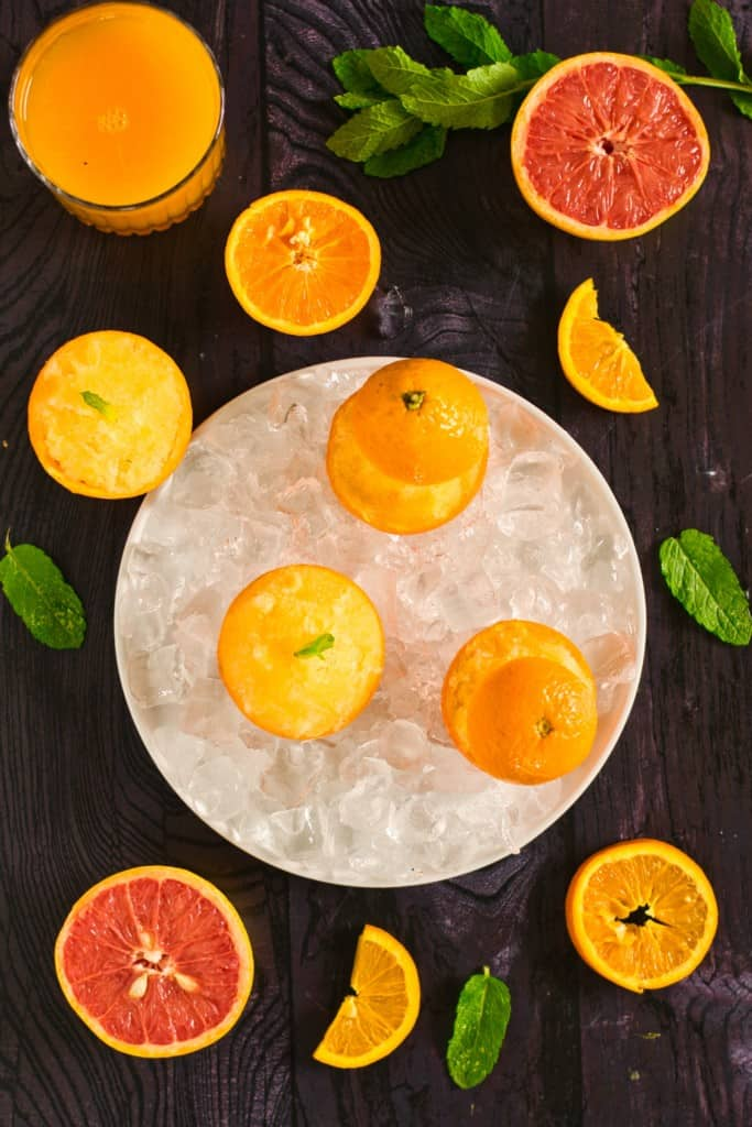 orange sorbet in orange peels in an iced dish with a glass container in the background