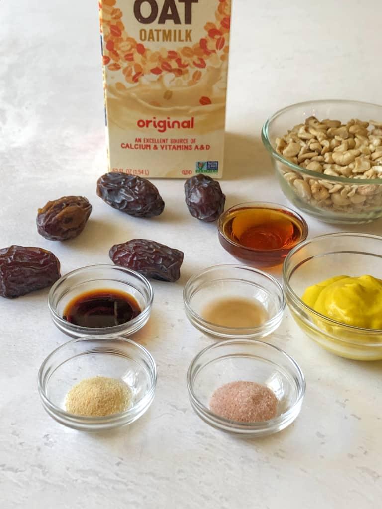 Ingredients for vegan honey mustard dressing including oat milk, Medjool dates, cashews, maple syrup, soy sauce, apple cider vinegar, yellow mustard, garlic powder, and salt