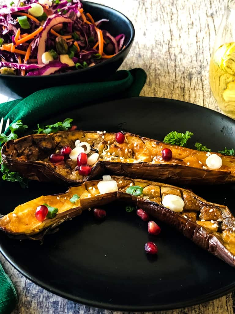 Two miso eggplant halves topped with sliced green onions, sesame seeds, and pomegranate seeds on a black plate with a side salad and white wine